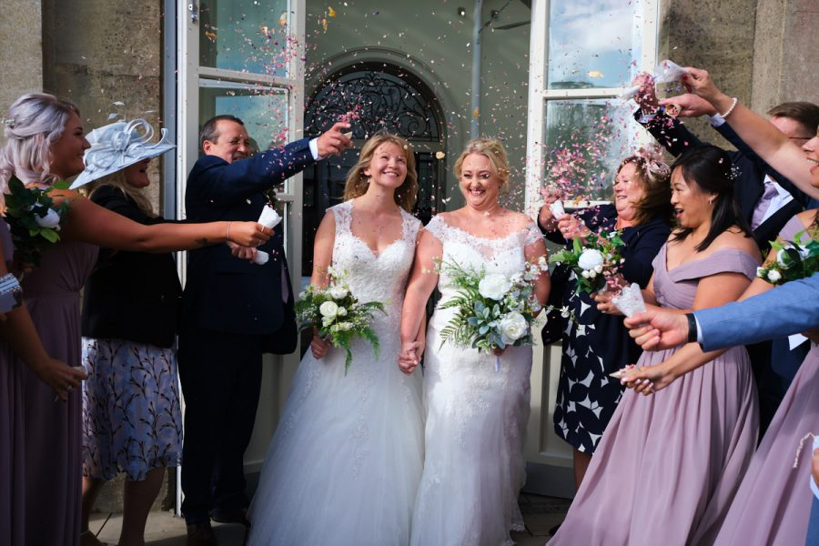 Two brides walk through confetti at their same sex wedding at Buxted Park Hotel.