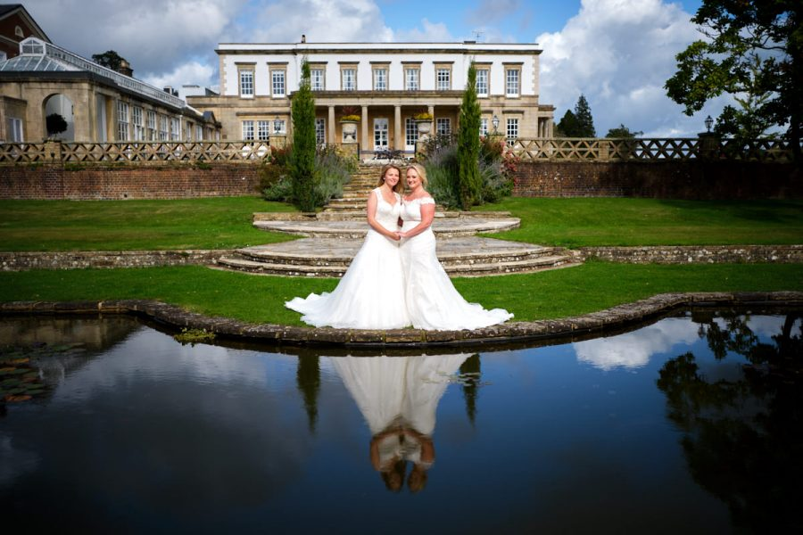 Two brides at their same sex wedding at Buxted Park Hotel pose for a photograph by the lake.