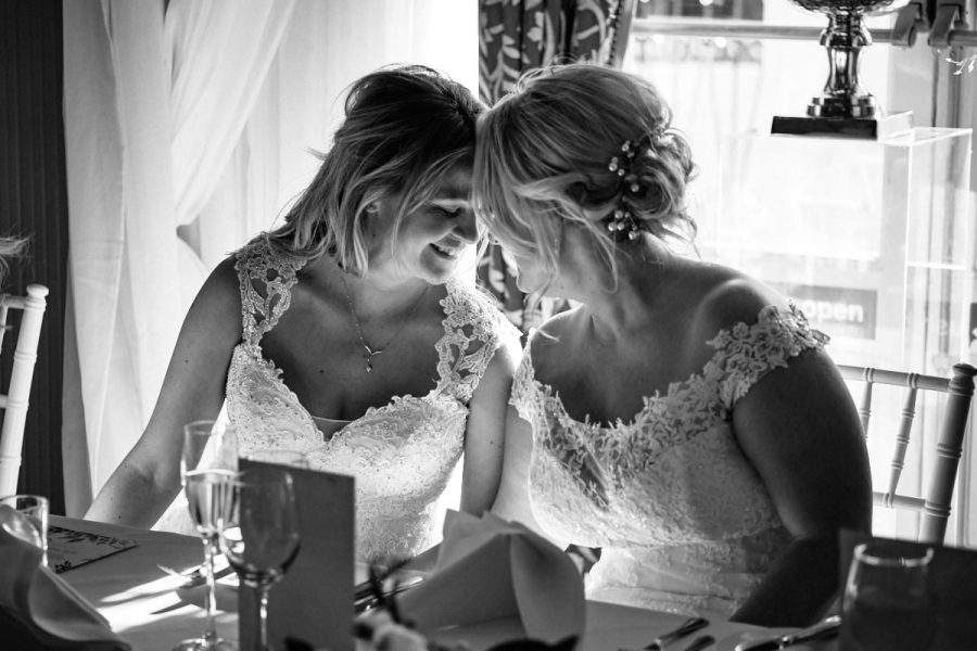 Two brides at a same sex wedding at Buxted Park Hotel share a moment together during the wedding breakfast.