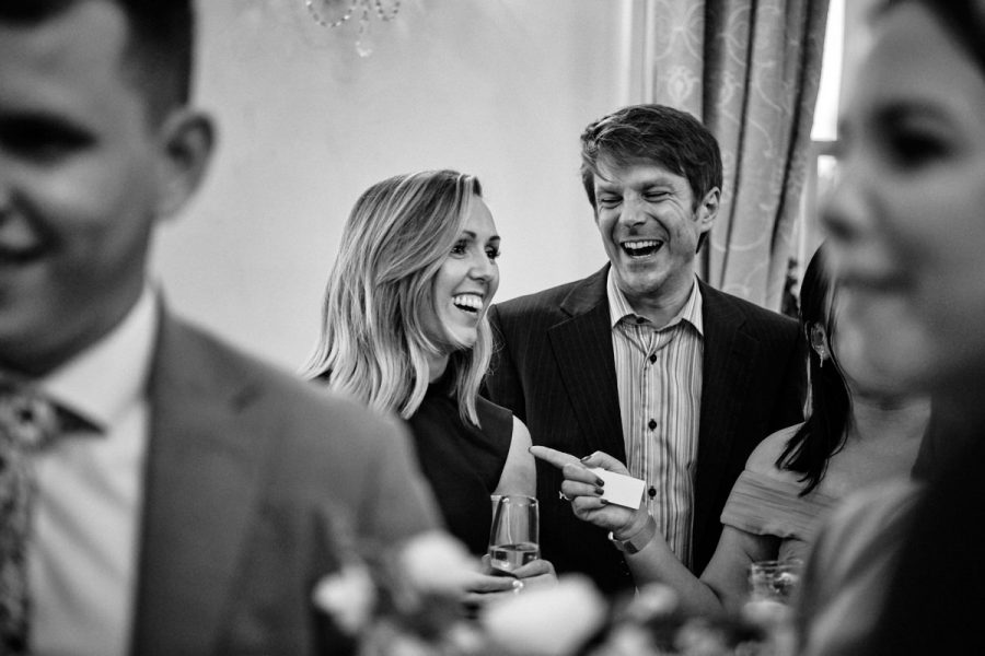 Guests laughing during the reception at a wedding at Buxted Park Hotel.